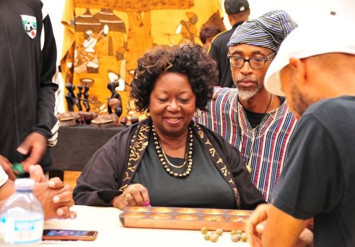 The Hon. Dr. Jean Augustine learns to play Oware with Andrew Martin.