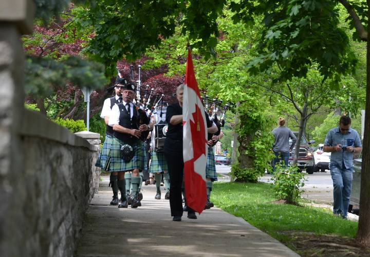 Dundas Pipes and Drums walking with flag to church concert
